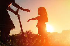 Happy family riding scooter and bike at sunset Stock Photos