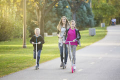 Happy family riding scooters together on a paved pathway outdoors Royalty Free Stock Photography