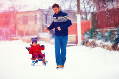 Happy family riding the sledge under winter snow, on village street Stock Images