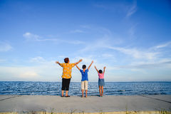 Happy family rises hands at Pranburi beach. Royalty Free Stock Photography