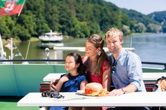 Family on river cruise looking at mountains from ship deck Stock Photo