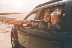 Happy family on a road trip in their car. Dad, mom and daughter are traveling by the sea or the ocean or the river. Summer ride by automobile Stock Images