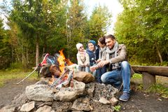 Happy family roasting marshmallow over campfire royalty free stock images