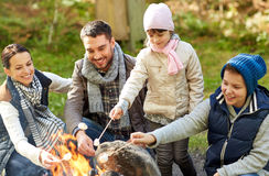 Happy family roasting marshmallow over campfire Royalty Free Stock Image