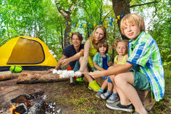 Happy family roasting marshmallows in the woods Stock Image