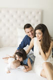 Happy family in the room. Family with a girl and a baby on the bed royalty free stock images