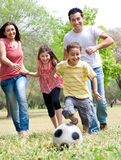 Happy family run. To the soccer ball in the park, outdoor stock images