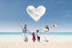 Happy family run at beach under love cloud