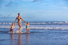 Happy family run with fun along sunset beach surf Royalty Free Stock Photo
