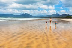 Happy family run by wide sand beach Stock Images
