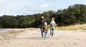 Happy family running along autumn beach stock photos
