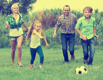 Happy family running with ball Royalty Free Stock Image