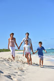 Happy family running on the beach Stock Image