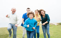 Happy family running on a green meadow Royalty Free Stock Photos