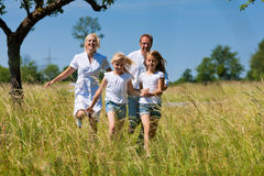Happy family running in the meadow Royalty Free Stock Photography