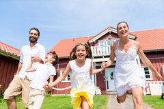 Happy family running on meadow in front of house Stock Images
