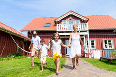 Happy family running on meadow in front of house royalty free stock images