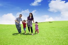 Happy family running in the meadow. Picture of happy family playing together while running in the meadow with beautiful sky background royalty free stock photos