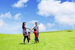 Happy family running in the meadow. Picture of happy family playing together while running in the meadow with beautiful sky background Stock Photo