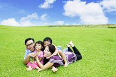 Happy family running in the meadow. Picture of happy family playing together while running in the meadow with beautiful sky background stock photos