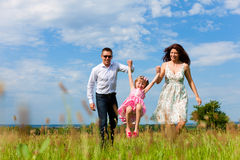 Happy family running on meadow in summer Stock Photography