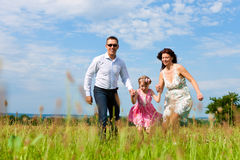 Happy family running on meadow in summer Royalty Free Stock Photo