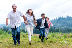 Happy family running outdoors Stock Photos