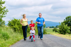 Happy family running for sport on street. Family of Little girl father and mother or mom and dad running on street in rural environment for sport Stock Image