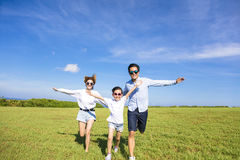 Happy family  running together on the grass Royalty Free Stock Photo