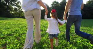 Happy family running together. In park stock footage