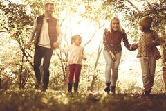 Happy family running trough park. Family walking in park together royalty free stock image