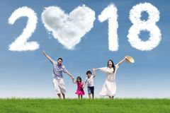 Happy family running under numbers 2018. Happy parents running with their children under clouds shaped numbers 2018 and heart. Shot in the meadow Stock Photo