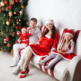 Happy family in Santa costumes celebrating Christmas. Royalty Free Stock Images