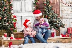 Happy family in Santa hat. Opening Christmas gift box royalty free stock photo
