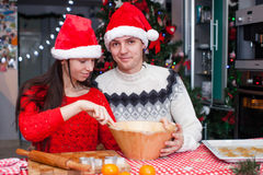 Happy family in Santa hats baking Christmas Royalty Free Stock Photography