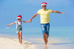 Happy family in Santa Hats during beach Christmas. Little girl and happy dad in Santa Hat at exotic beach Royalty Free Stock Images