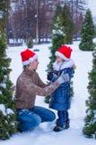 Happy family in Santa hats with christmas tree Stock Image