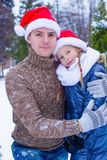 Happy family in Santa hats with christmas tree Royalty Free Stock Photography