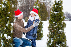 Happy family in Santa hats with christmas tree Royalty Free Stock Image