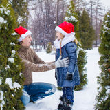 Happy family in Santa hats with christmas tree Stock Photo