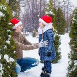 Happy family in Santa hats with christmas tree Stock Photo
