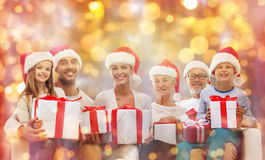 Happy family in santa hats with gift boxes. Christmas, generation, holidays and people concept - happy family in santa helper hats with gift boxes sitting on Stock Images