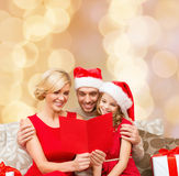 Happy family in santa hats with greeting card Royalty Free Stock Photos