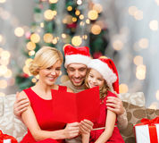 Happy family in santa hats with greeting card Royalty Free Stock Photo