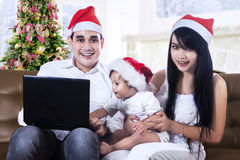 Happy family in santa hats with laptop Stock Photography