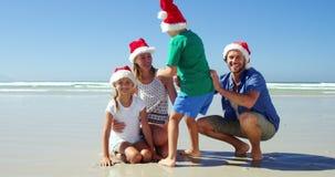 Happy family in santa hats posing at beach