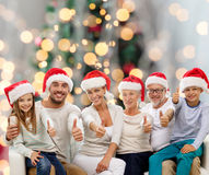 Happy family in santa hats showing thumbs up Stock Image