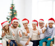 Happy family in santa hats showing thumbs up Royalty Free Stock Photos
