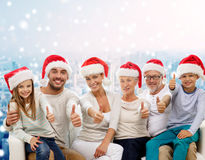 Happy family in santa hats showing thumbs up Royalty Free Stock Images
