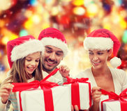 Happy family in santa hats sitting with gift boxes royalty free stock photos